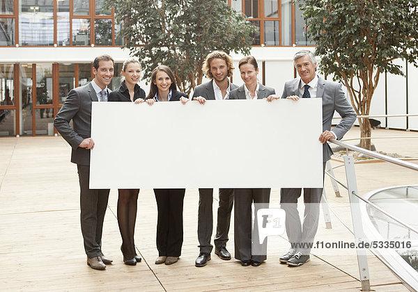 Sechs Personen halten Transparent