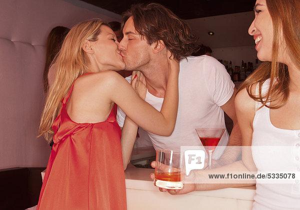 Pärchen küsst sich  Frau sieht zu