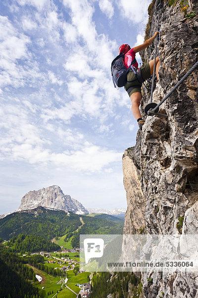 Kletterer im Stevia Klettersteig im Langental in Gröden  hinten der Langkofel und das Dorf Wolkenstein  Dolomiten  Südtirol  Italien  Europa Kletterer im Stevia Klettersteig im Langental in Gröden, hinten der Langkofel und das Dorf Wolkenstein, Dolomiten, Südtirol, Italien, Europa