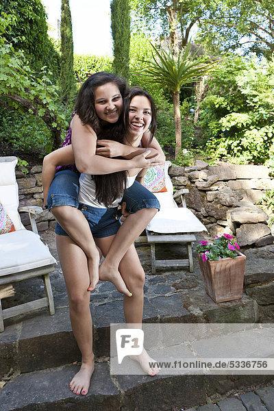 Zwei Mädchen  etwa 13 Jahre und 18 Jahre  eine trägt die andere Huckepack