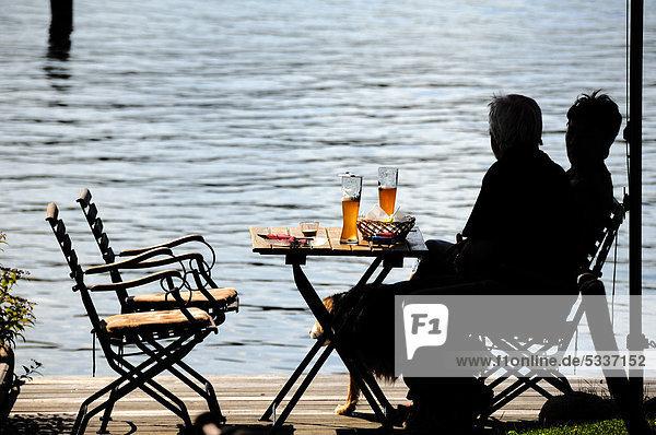Brotzeit am See  zwei Personen am Tisch als Silhouette erkennbar  Ratzeburger See  Ratzeburg  Schleswig-Holstein  Deutschland  Europa