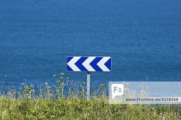 Schild mit Richtungspfeilen nach links vor Gewässer