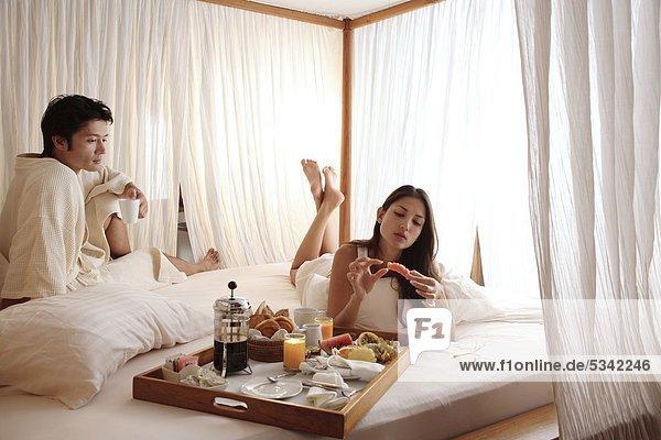 Couple having Frühstück im Bett bei Coco Palm Dhuni Kolhu Resort auf den Malediven