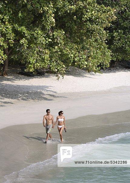 Couple walking on Emerald Bay at Pangkor Laut Resort in Malaysia
