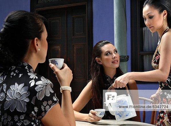 Frauen  die mit chinesischen Tee am Cheong Fatt Tze Mansion in Penang  Malaysia