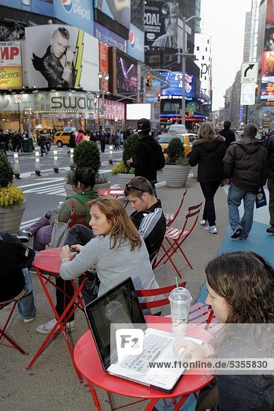 New York  New York City  NYC  Midtown  Manhattan  Times Square  Theatre District  woman  pedestrian plaza  table  outdoor hot spot  people watch  laptop computer  street scene