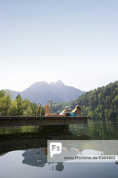 Junge Frauen auf Steg am Schwansee bei Füssen  Allgäu  Bayern  Deutschland  Europa