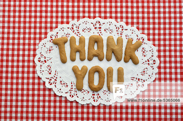 Thank you  written in alphabet biscuits on paper doily