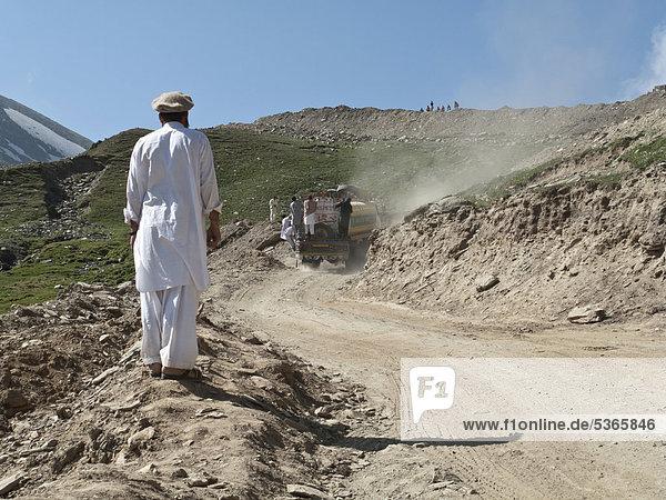 Einheimischer Mann sieht zu  wie seine Freunde über den Babusar Pass mitgenommen werden  Chillas  Nordwestliche Grenzprovinz  Pakistan  Südasien  Asien