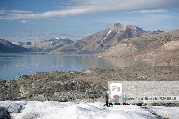 Gletscherwanderer auf dem Gletscher Nordenskiöldbreen  hinten die Siedlung Pyramiden  Billefjord  Spitzbergen  Norwegen  Skandinavien  Europa