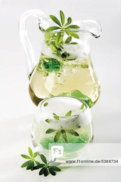 Karaffe und Glas mit Waldmeister-Bowle Karaffe und Glas mit Waldmeister-Bowle