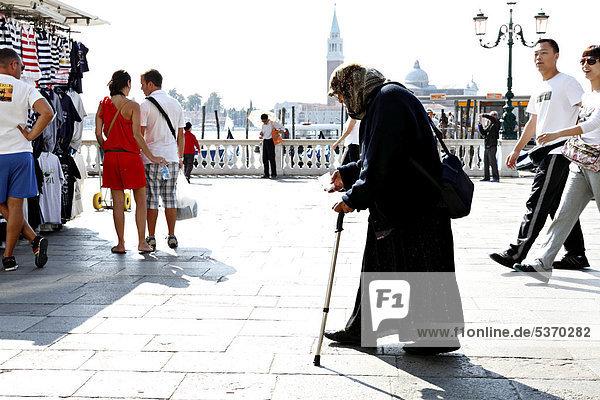 Lady begger walking amongst tourists  Venice  Italy  Europe