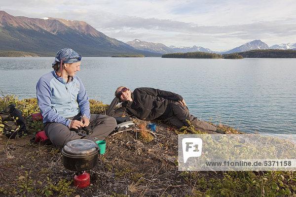 Zwei junge Frauen kochen mit Campingkocher  entspannen  Atlin Lake See  British Columbia  Kanada  Amerika