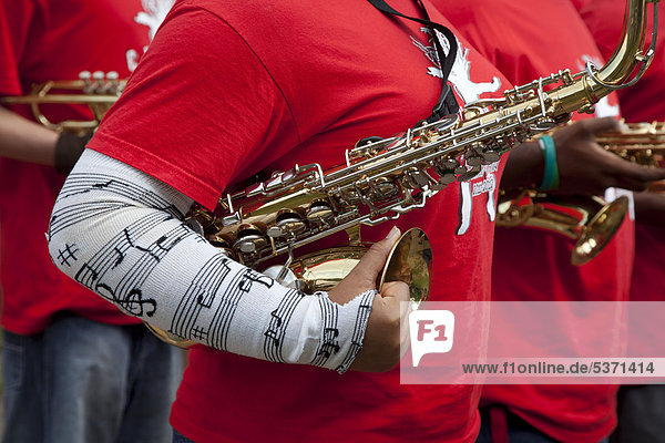 Saxophone being carried by a member of The Everett High School Marching Band  Lansing  Michigan  USA