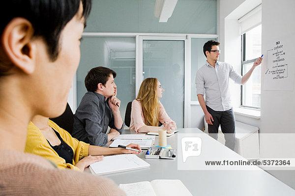 Junge Menschen am Konferenztisch  sitzt Man erklären Diagramms