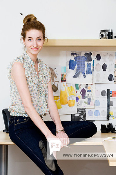 Junge Modedesignerin auf dem Schreibtisch sitzend  Portrait