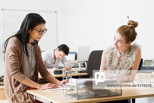 Junge Frauen im Büro  im Hintergrund arbeitender Mann