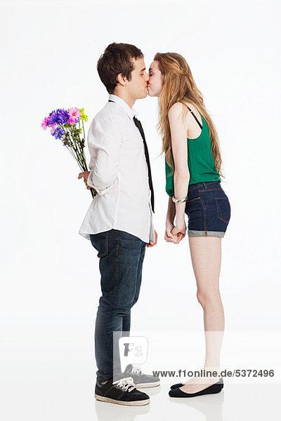Junges Paar küsst sich vor weißem Hintergrund
