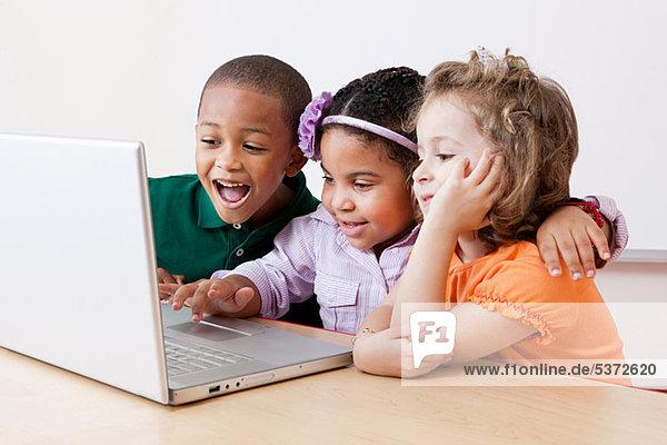Drei Kinder schauen gemeinsam auf den Laptop