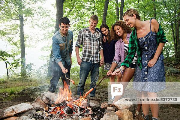 Freunde beim Kochen am Lagerfeuer im Wald