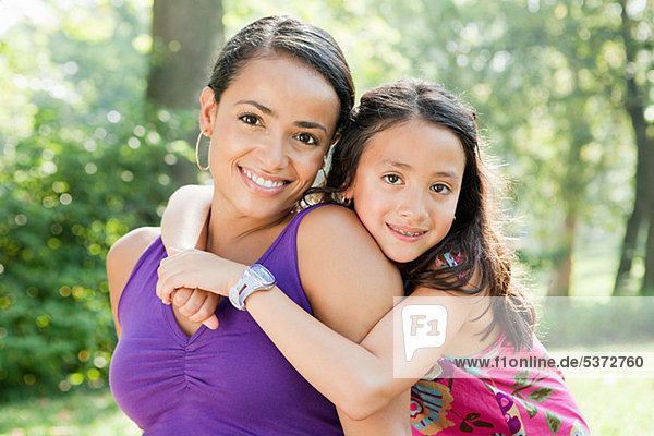 Mother and daughter smiling in park  portrait