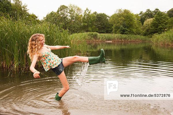 Teenagermädchen waten in die Mitte eines Sees mit überfließenden Gummistiefeln. Teenagermädchen waten in die Mitte eines Sees mit überfließenden Gummistiefeln.