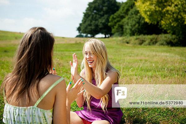 Junge Frauen spielen Patacake in einem Feld