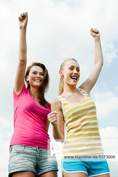 Junge Frauen jubeln with Arms raised