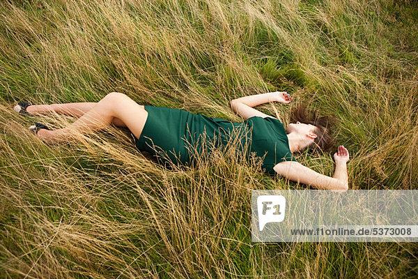 Young Woman lying down in einem Feld in ein grünes Kleid