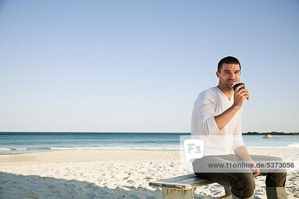 Man trinken Kaffee am Strand