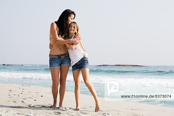 Mother and daughter hugging on a beach