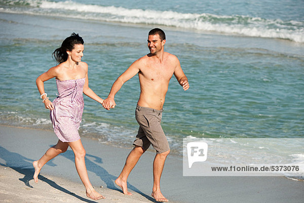 Junges Paar  die entlang den Rand des Wassers am Strand
