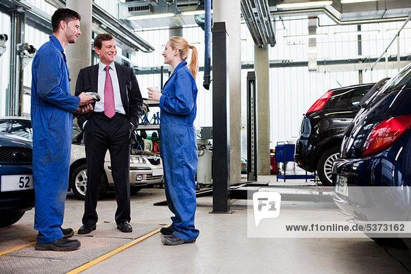 Businessman with two car mechanics in repair garage