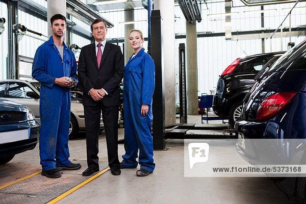 Kaufmann mit Mechanik in Reparaturwerkstatt