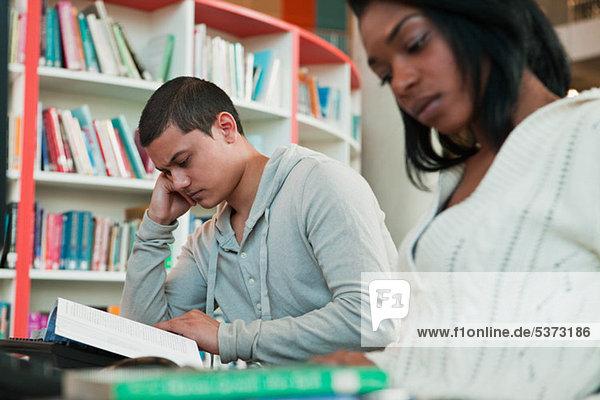 Studenten lesen Lehrbücher in College-Bibliothek