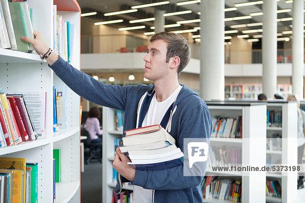Universitätsstudent wählt Lehrbücher in der Bibliothek aus