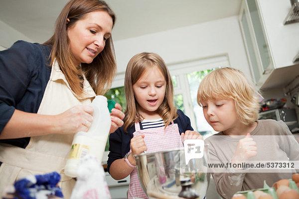 Mittlere erwachsene Frau beim Backen mit Sohn und Tochter in der Küche