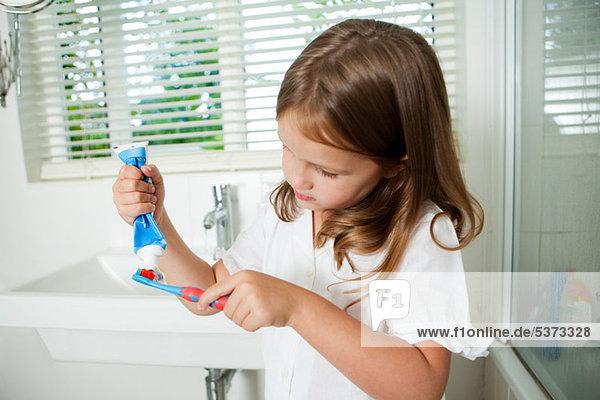Mädchen beim Auftragen von Zahnpasta auf die Bürste im Bad