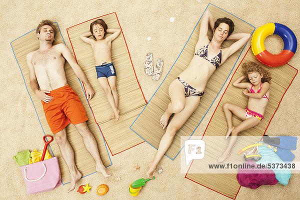 Deutschland  Künstliche Strandszene mit auf Matte liegender Familie