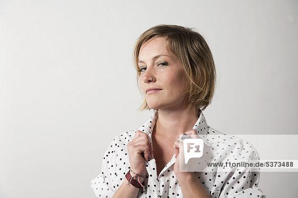 Frau vor weißem Hintergrund stehend  lächelnd  Portrait