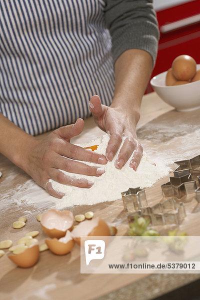 Frau macht Teig für Kekse in der Küche