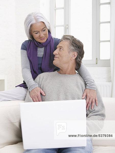 Deutschland  Hamburg  Seniorenpaar mit Laptop schaut sich an  lächelnd