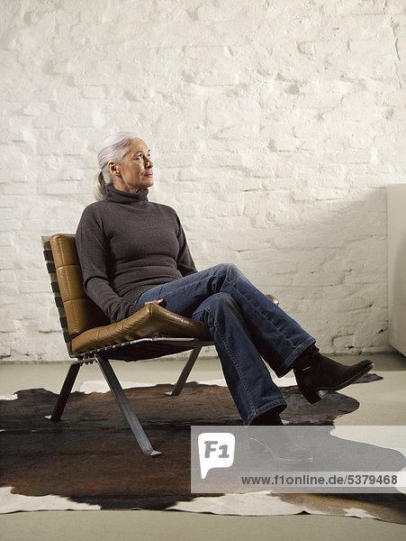 Seniorin entspannt sich auf dem Stuhl