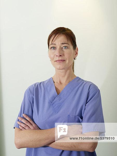 Deutschland  Hamburg  Ärztin in Peelings mit gekreuzten Armen  Portrait