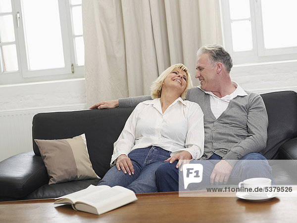 Deutschland  Hamburg  Paar auf Sofa schaut sich an  lächelnd