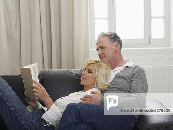 Deutschland  Hamburg  Paar Lesebuch auf Sofa