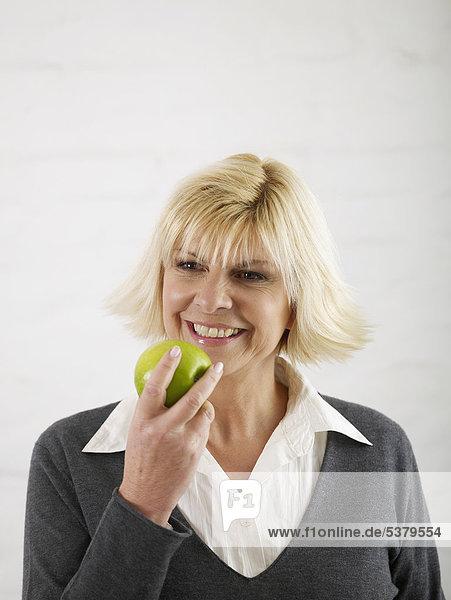 Reife Frau mit Apfel  lächelnd