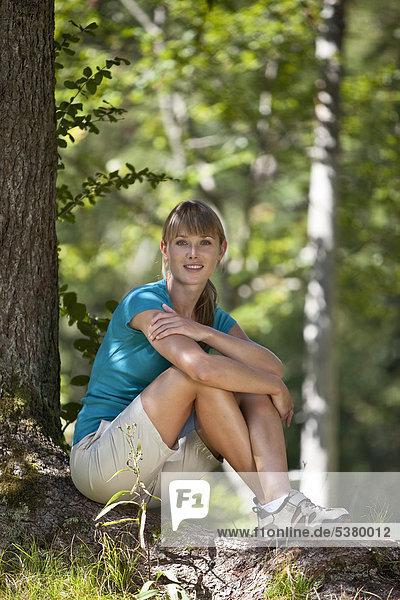 Deutschland  Oberbayern  Junge Frau unter Baum  lächelnd  Porträt