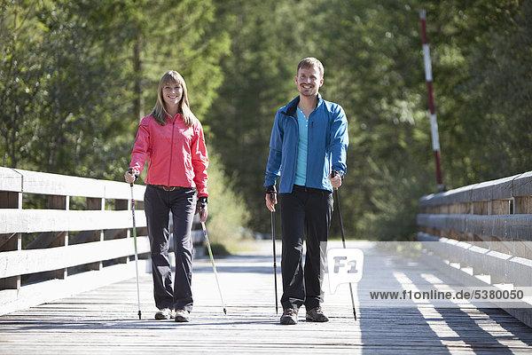 Deutschland  Oberbayern  Paar mit Nordic Walking auf der Brücke