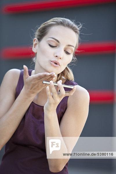Junge Frau mit Handy-Blaskuss
